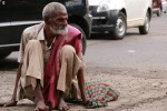 A beggar sits out the front of Chhatrapati Shivaji Terminus.