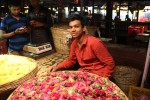 A young man sells India's iconic marigold flower at the Dadar Flower Markets.