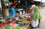 Indonesian women purchasing fresh chillies from a stall on the side of the alleyway
