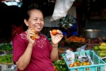 A joyful Indonesian lady selling her produce